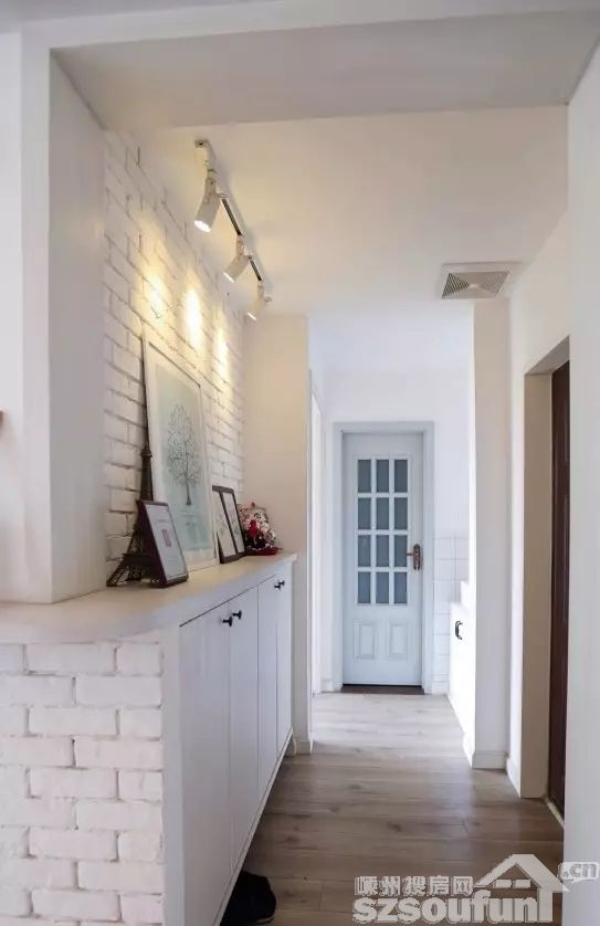 玄关处是白色的文化砖墙设计,白色的鞋柜与墙面视觉上融为一体